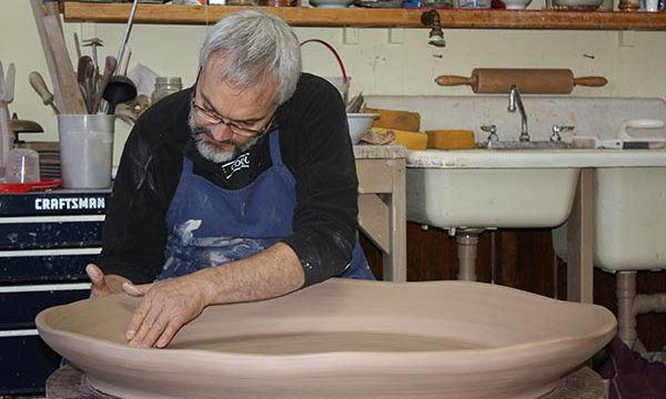 Jeff Diehl throws a large tray on the wheel | by Donna Diehl